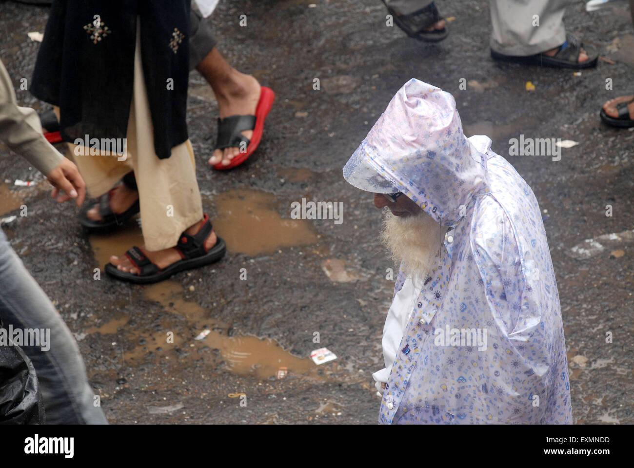 Einen alten Mann Cover selbst mit einem Regenmantel bei Regen in der Nähe von Kurla Station; Bombay jetzt Mumbai; Stockbild
