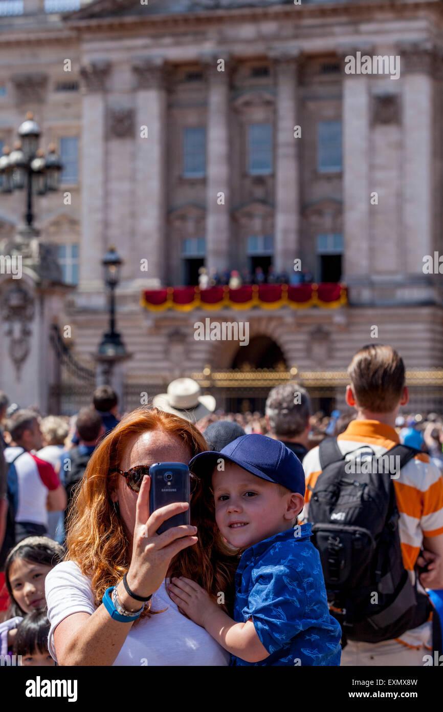 Ein Besucher braucht ein Selfie von sich selbst und Kind außerhalb der Buckingham Palace, London, England Stockbild