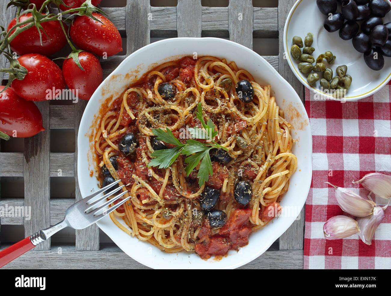 italienische Küche: Pasta mit Tomaten, Oliven und Kapern, genannt Puttanesca Stockbild