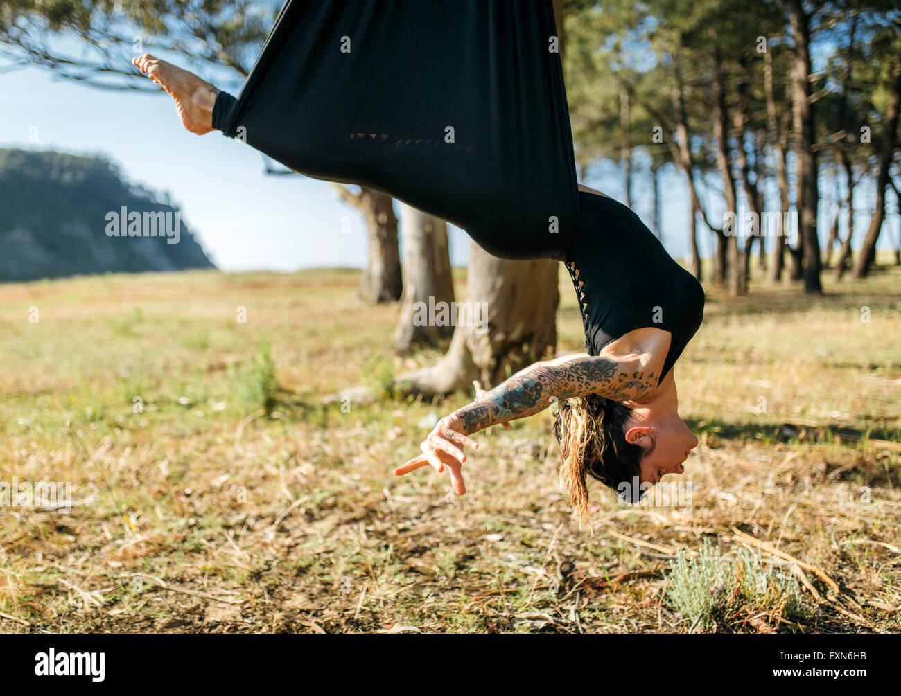 Frau praktizierender aerial Yoga im freien Stockbild