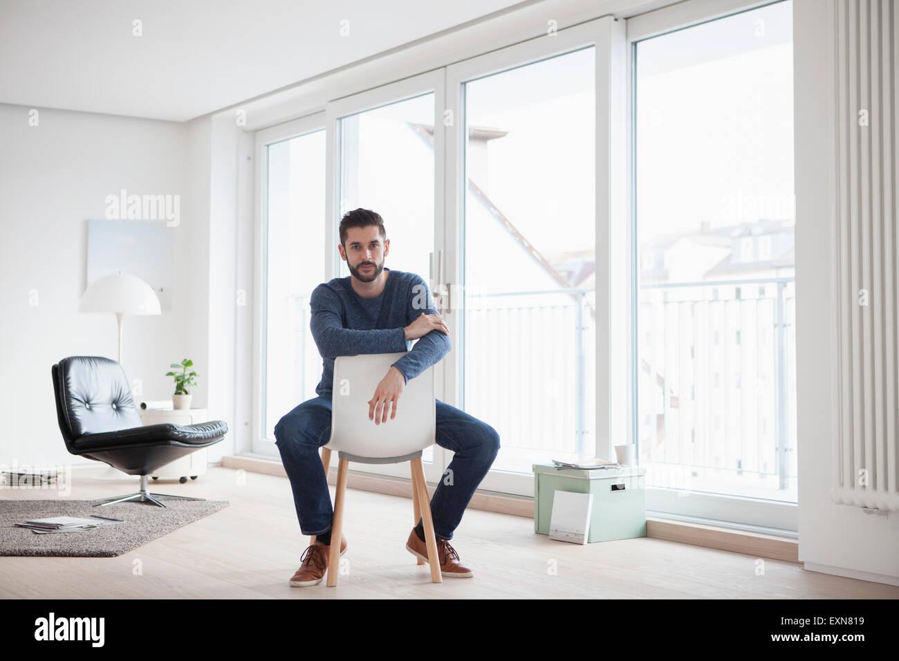 Junger Mann sitzt auf einem Stuhl in seinem Wohnzimmer Stockfoto ...