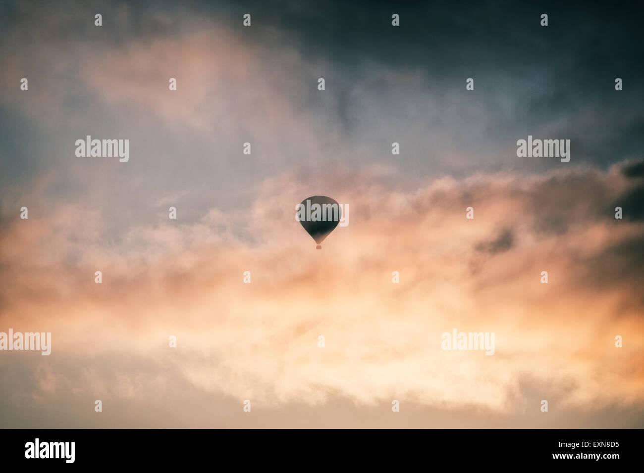 ein Heißluftballon in den Sonnenaufgang Stockbild