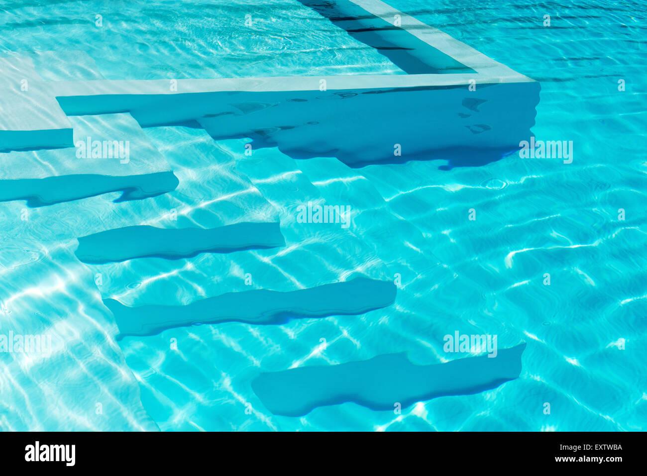 Unterwasser Schritte in einen glitzernden blauen Swimmingpool mit Reflexionen Stockbild