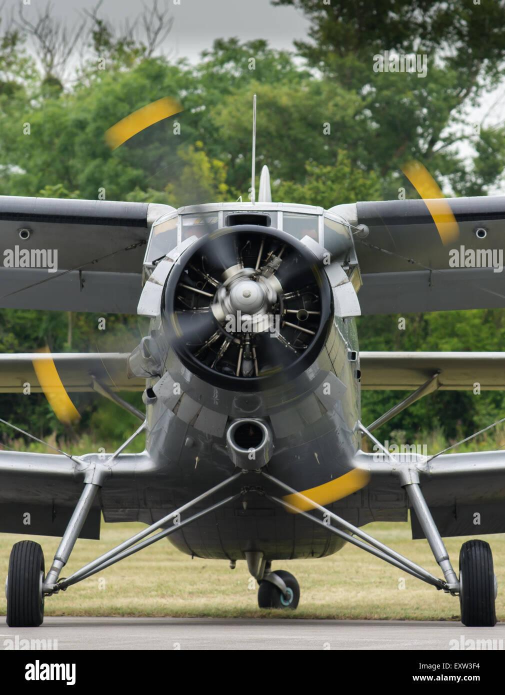 Vorderansicht der eine alte Oldtimer Doppeldecker mit drehendem Propeller, warten auf einem Flugplatz kurz vor dem Stockbild