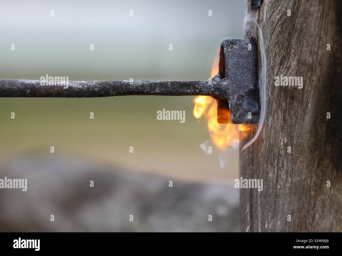 Ein Brandeisen markiert einen Holzpfosten mit dem Buchstaben A Stockbild