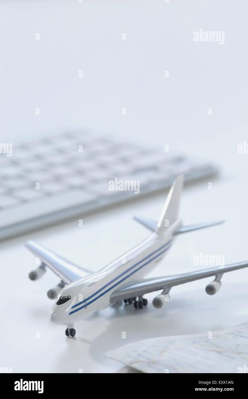 Modellflugzeug, Tastatur und Karte auf Schreibtisch Stockfoto
