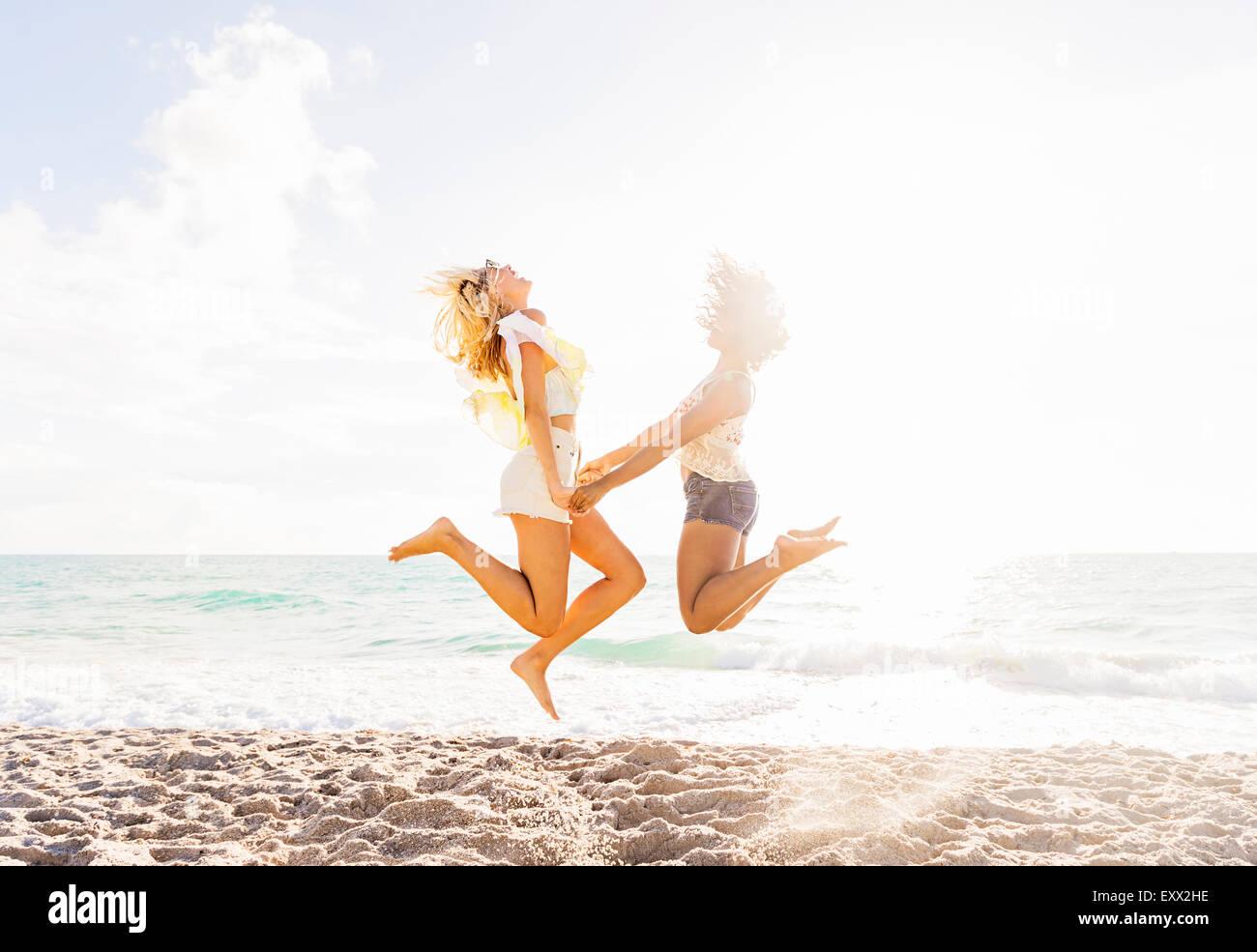 Freundinnen am Strand springen Stockbild