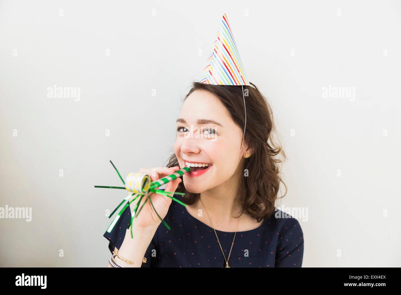 Lächelnde junge Frau mit Partei Horn Gebläse Stockbild