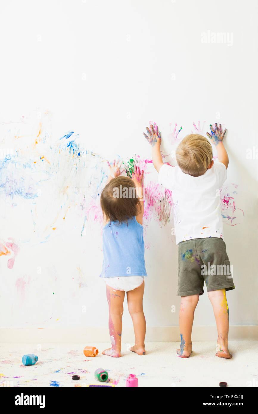 Kinder (2-3) Malerei auf Wand, Rückansicht Stockbild