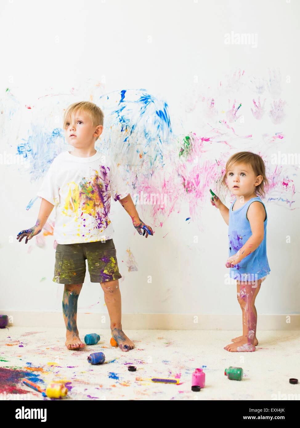 Kinder (2-3) an Wand malen Stockbild