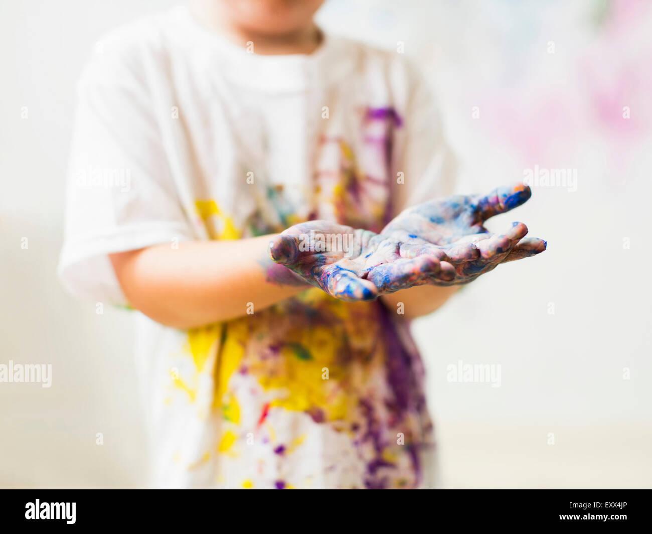 Jungen (2-3) zeigt die Hände in Farbe Stockbild