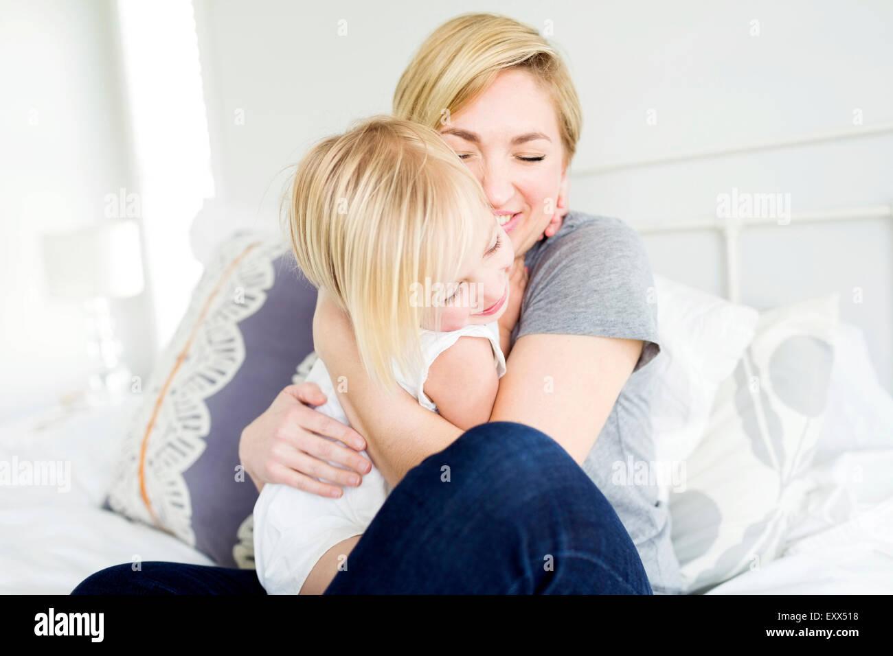 Frau umarmt Tochter im Schlafzimmer (2-3) Stockbild