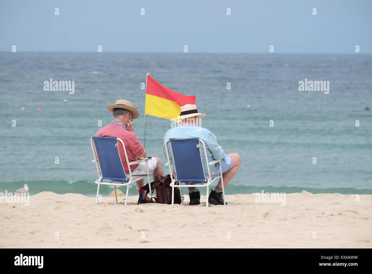 St. Ives, Cornwall, UK: Zwei Männer mittleren Alters tragen Jumper und Strohhüte saß am Strand camping Stockbild