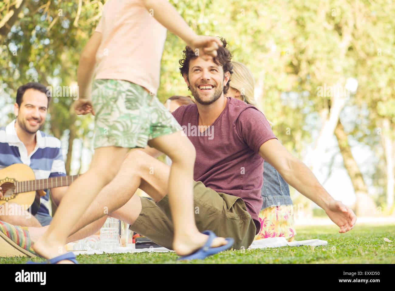 Mann beim Picknick beobachten Kinder spielen Stockbild