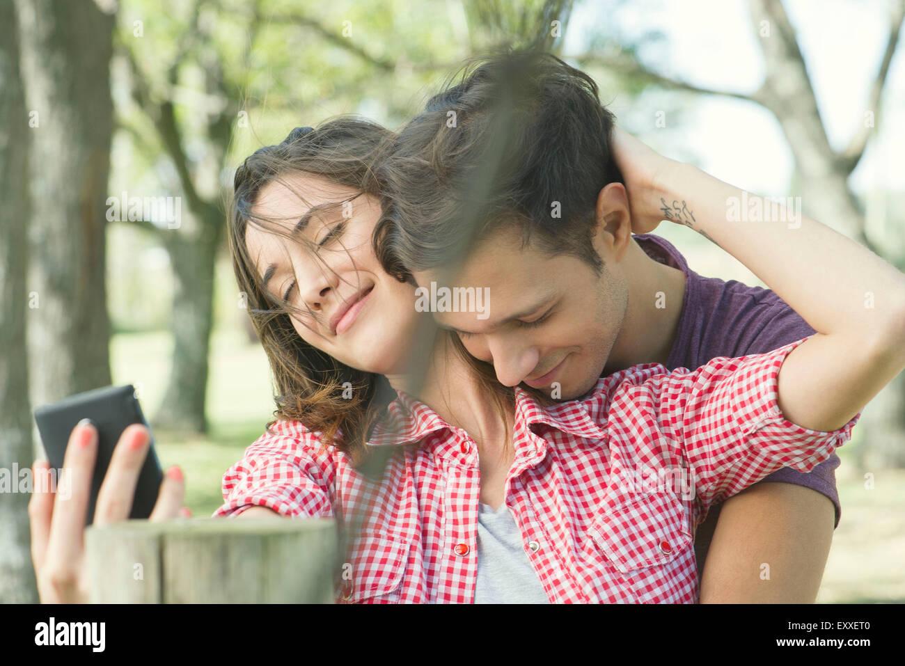 Paar im freien umarmen, posiert für ein selfie Stockbild