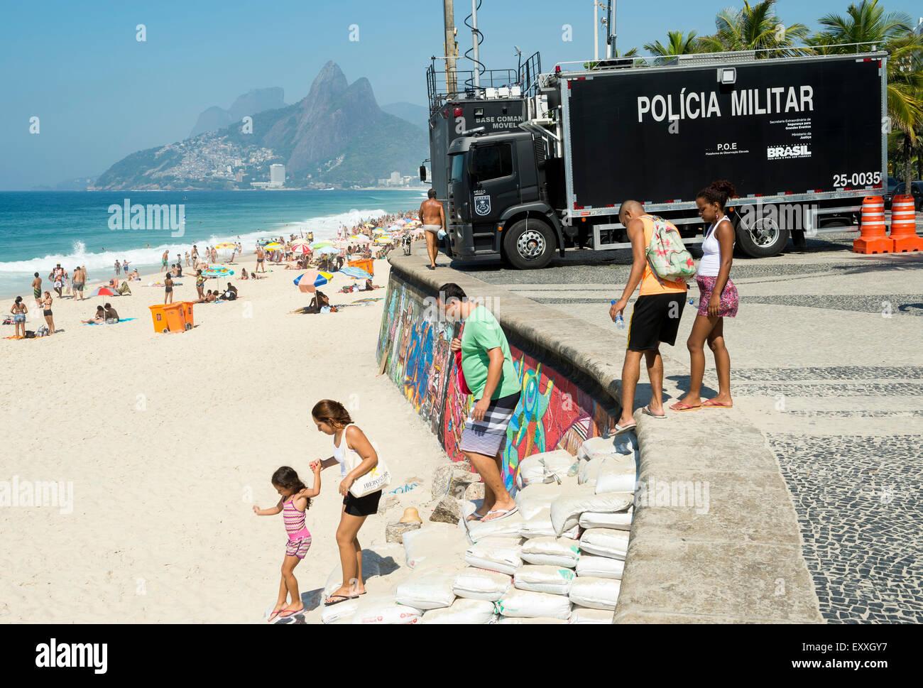 RIO DE JANEIRO, Brasilien - 20. Januar 2015: Beachgoers Arpoador Beach vor polizeilichen Überwachung LKW ankommen. Stockfoto