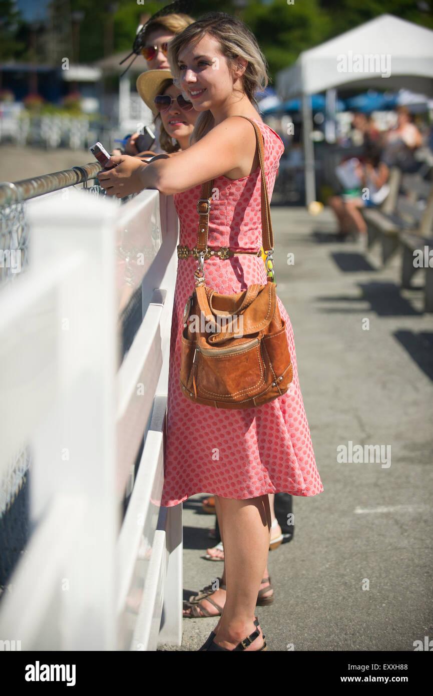 Weibliche Zuschauer im Sommerkleid an einem eingezäunten Reling ein Pferd Rennen im Hastings Park Vancouver Stockbild