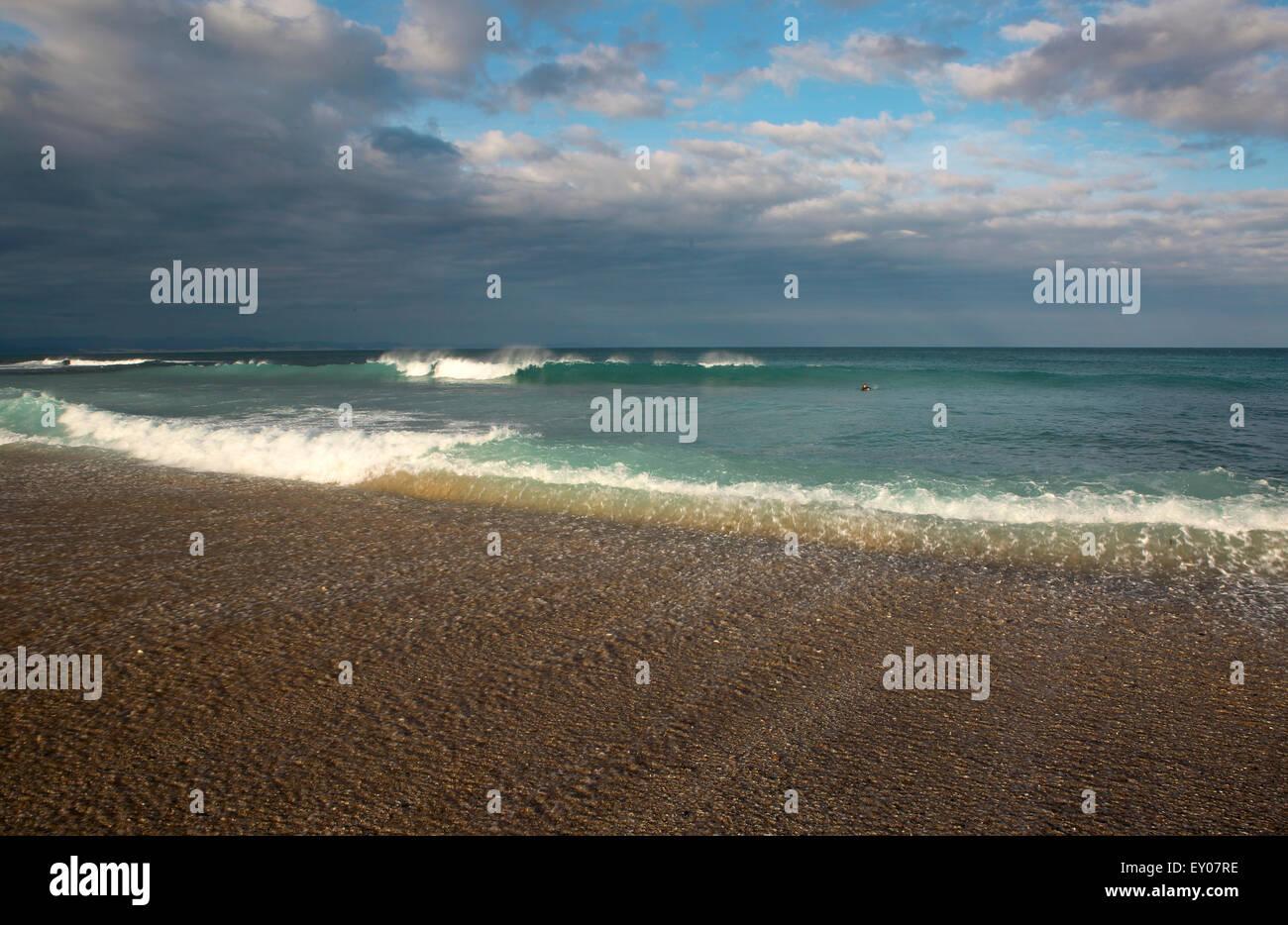 Meereswellen und Wolkengebilde am Sandstrand in Jeffreys Bay, Südafrika Stockbild