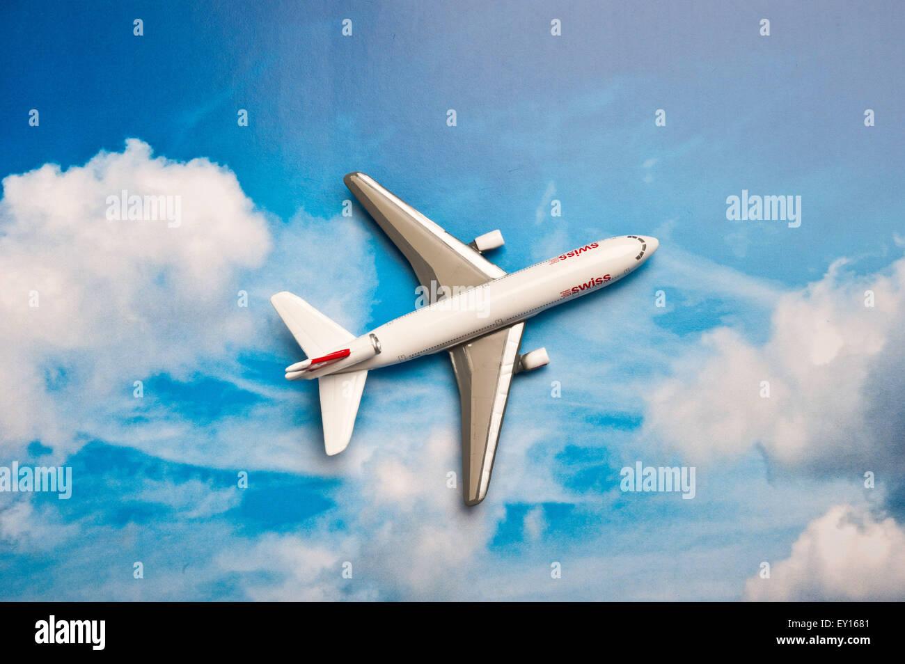 Miniatur-Spielzeugflugzeug Swissair auf einem gedruckten Himmelshintergrund Stockbild