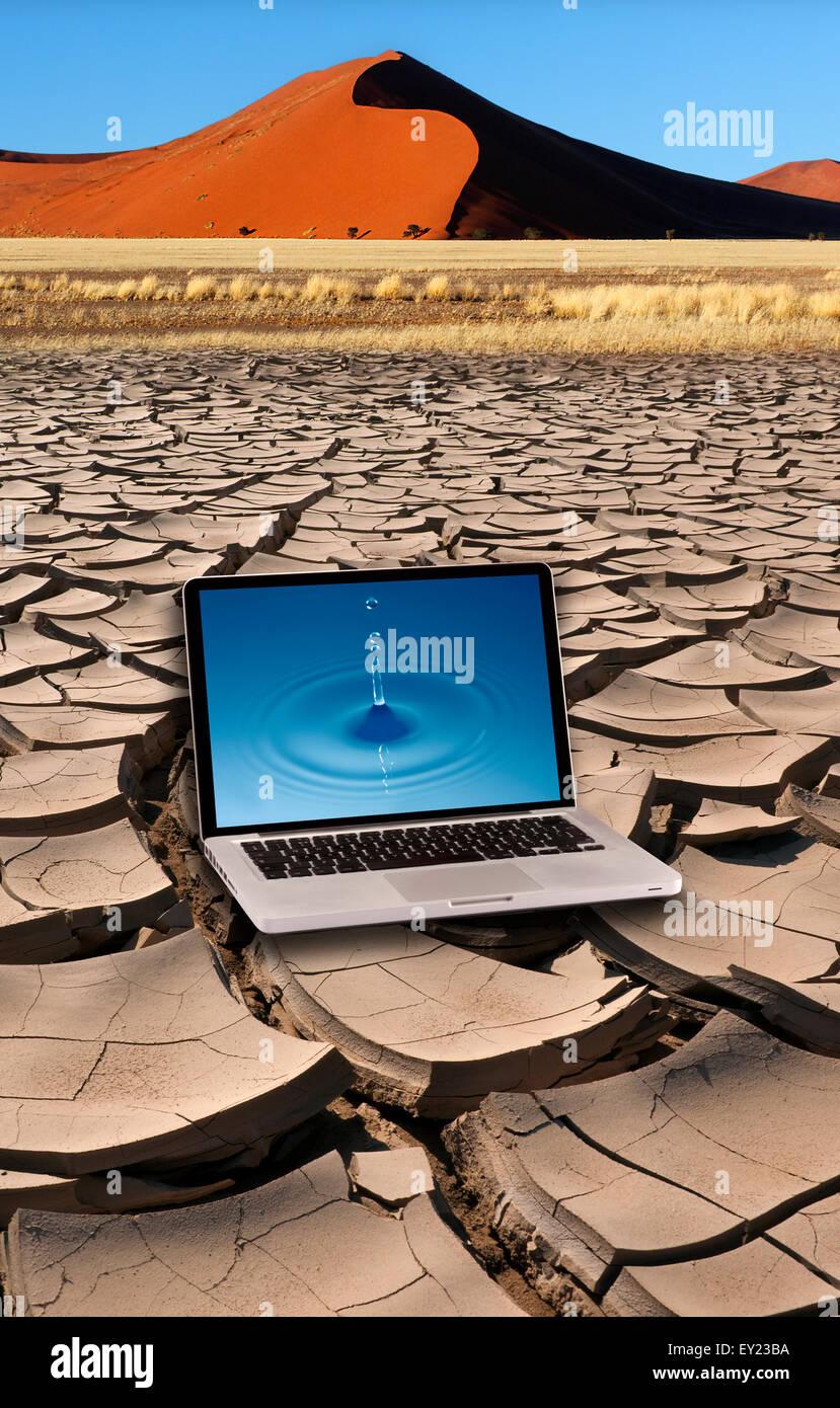 Laptop mit reinen Wassertropfen auf dem Bildschirm auf der trockenen Erde mit Sand Dune. Stockbild
