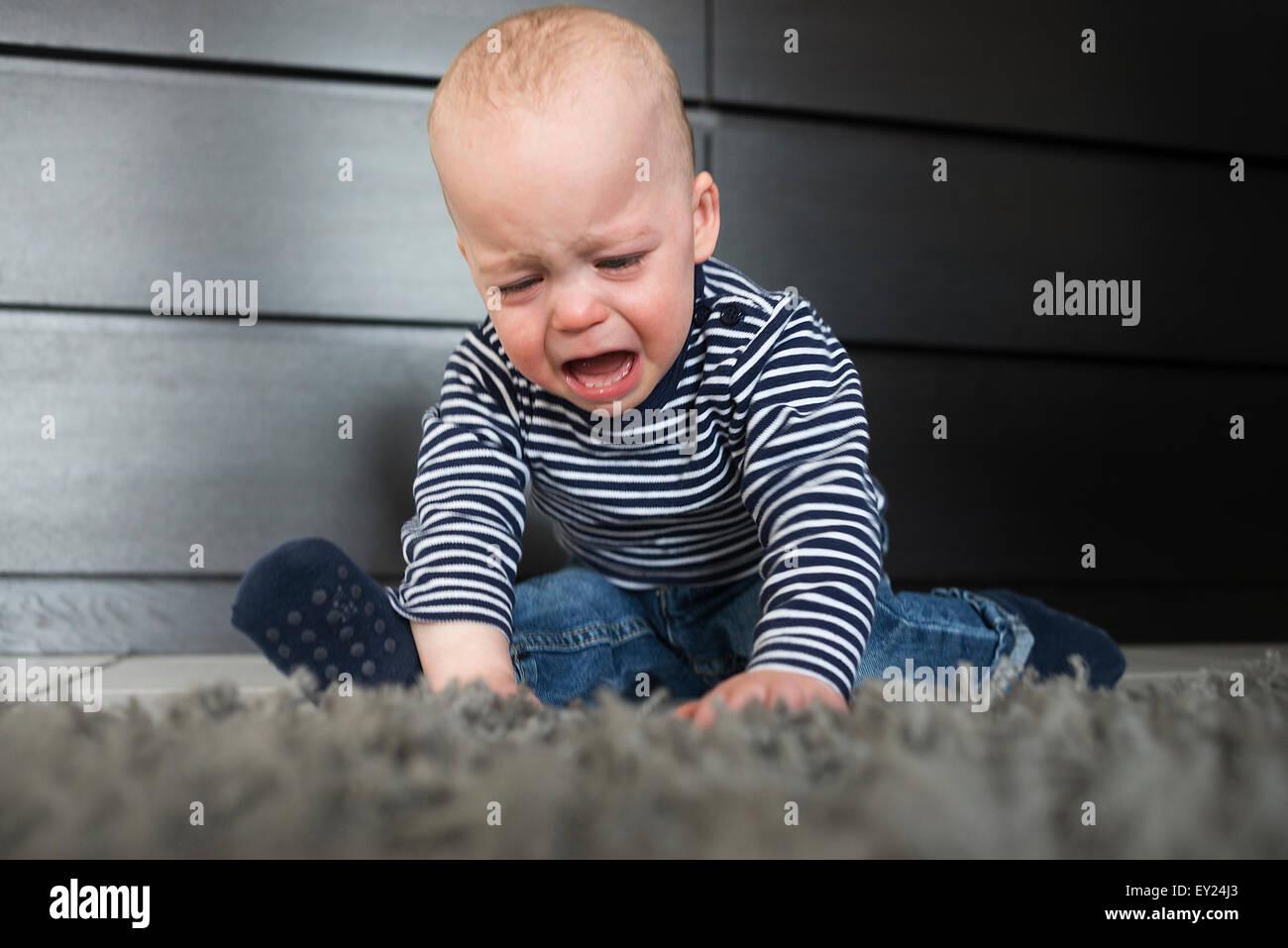 Schreiendes Baby Junge sitzt auf Teppich im Wohnzimmer Stockfoto ...