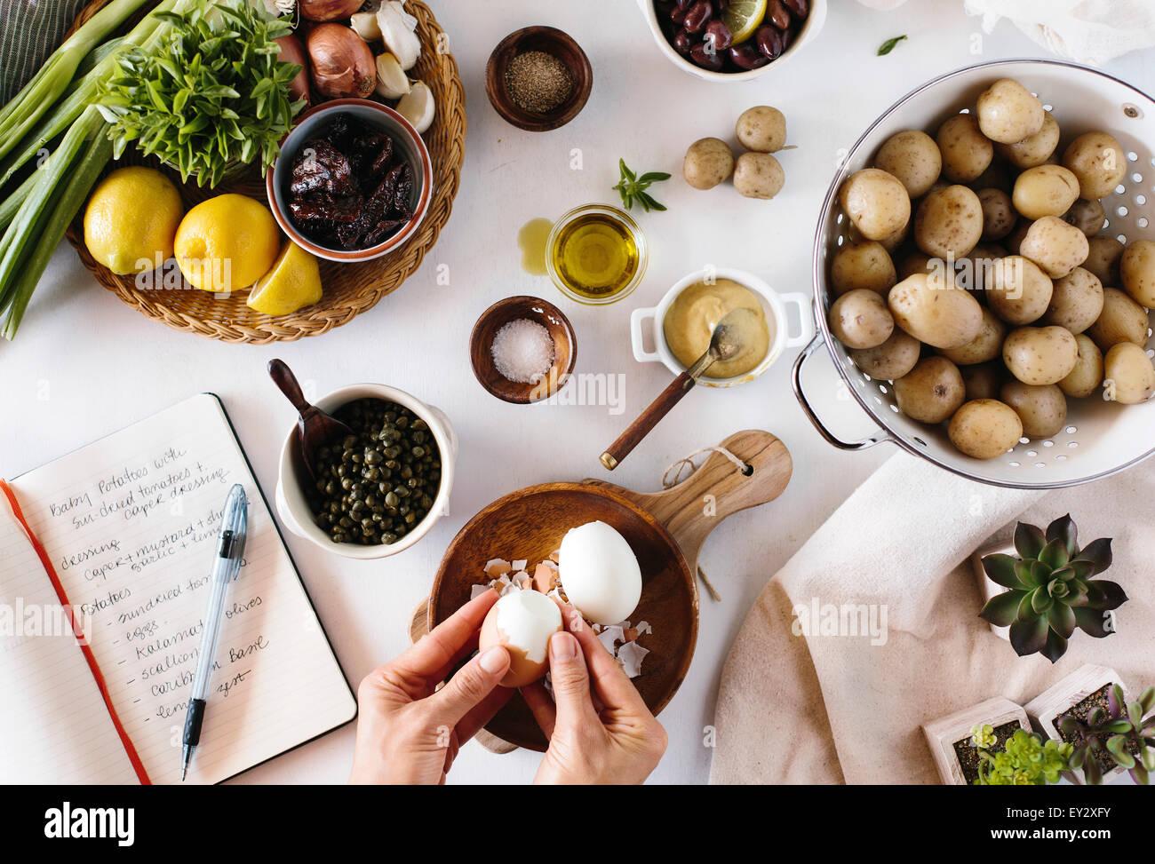 Eine Person schält Eiern für ein Baby-Kartoffelsalat Stockbild
