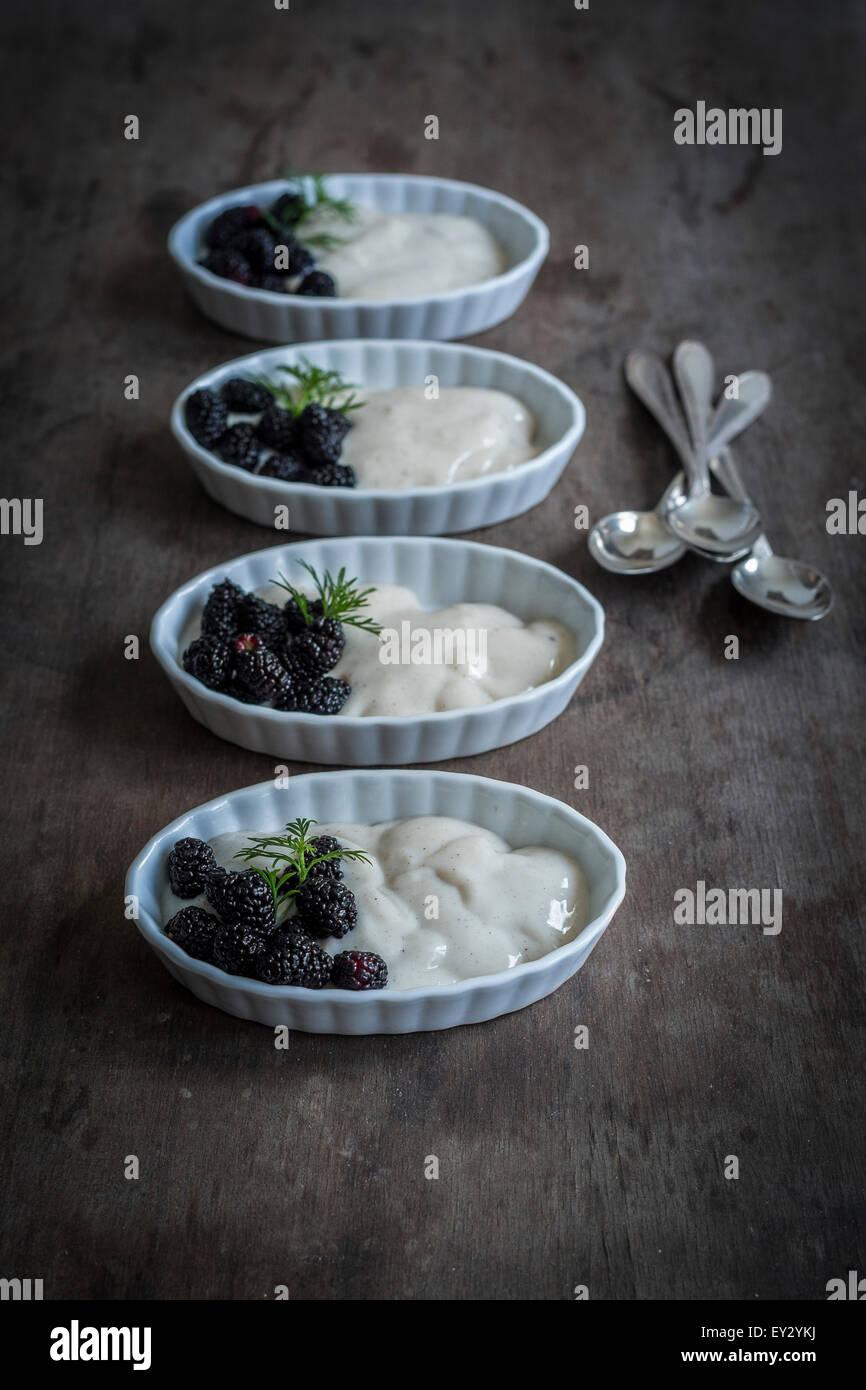 Maulbeeren und Vanillecreme in China Gerichte auf hölzernen Hintergrund Stockbild