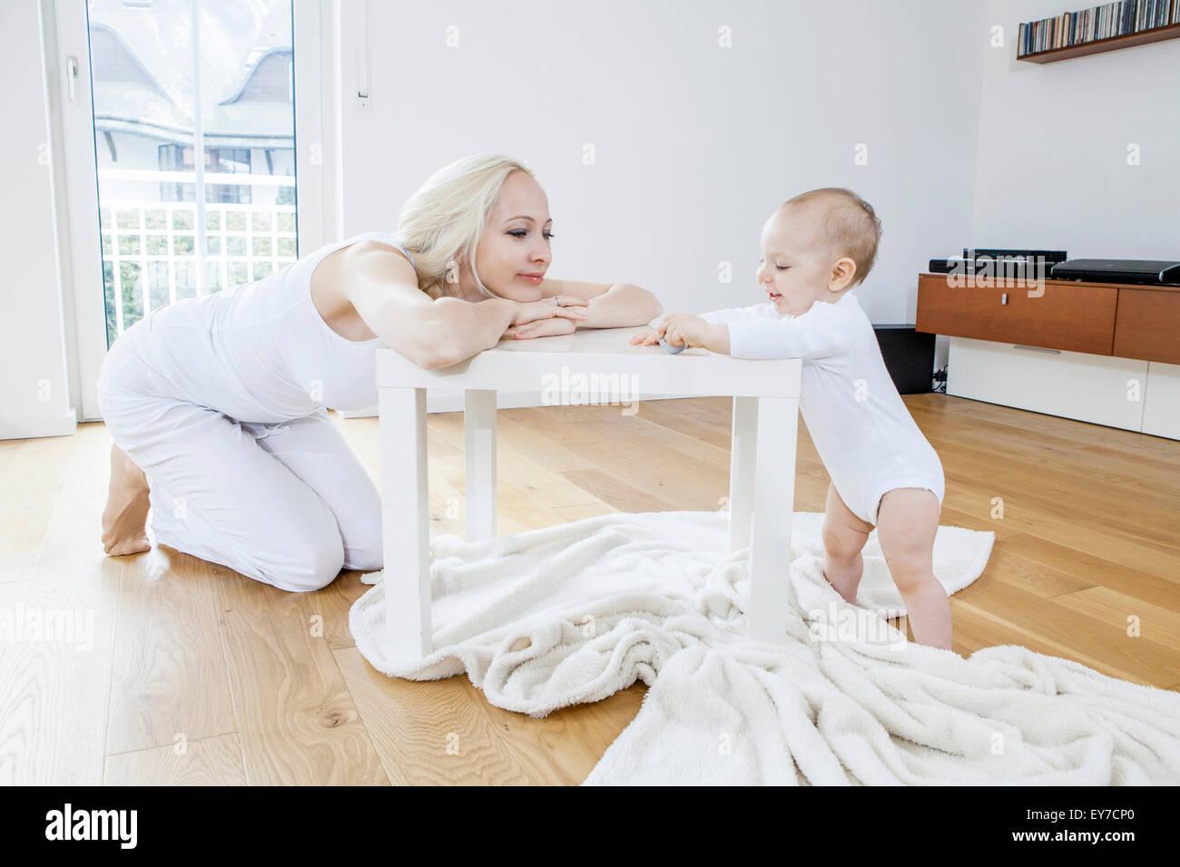 Mutter und Baby spielen im Wohnzimmer Stockbild