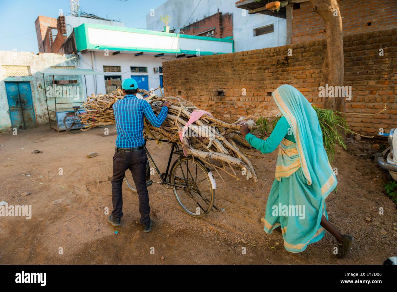 Mann und Frau mit Brennholz auf einem Fahrrad in Khajuraho, Madhya Pradesh, Indien Stockbild