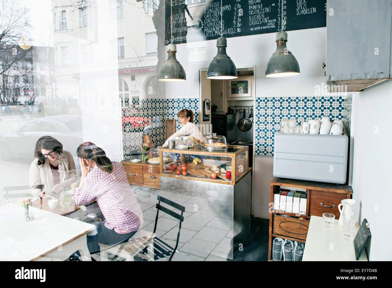 Gäste und Kellnerin im café Stockbild
