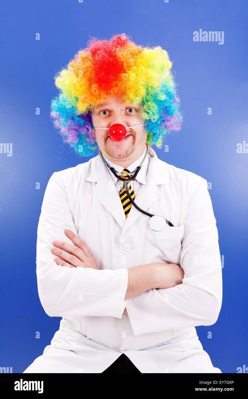 Lustiger Clown Doktor auf blau, tragen bunte Perücke und roter Ball Nase Stockfoto