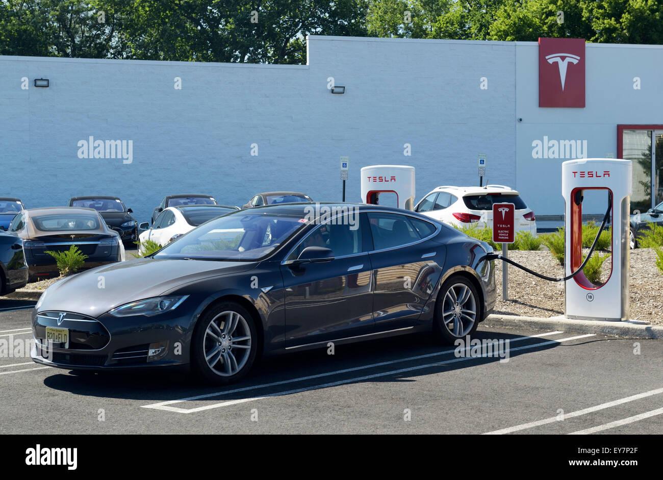 Ladestation mit einem Tesla Limousine Elektroauto eingesteckt. Tesla-Händler, Paramus, NJ Stockfoto