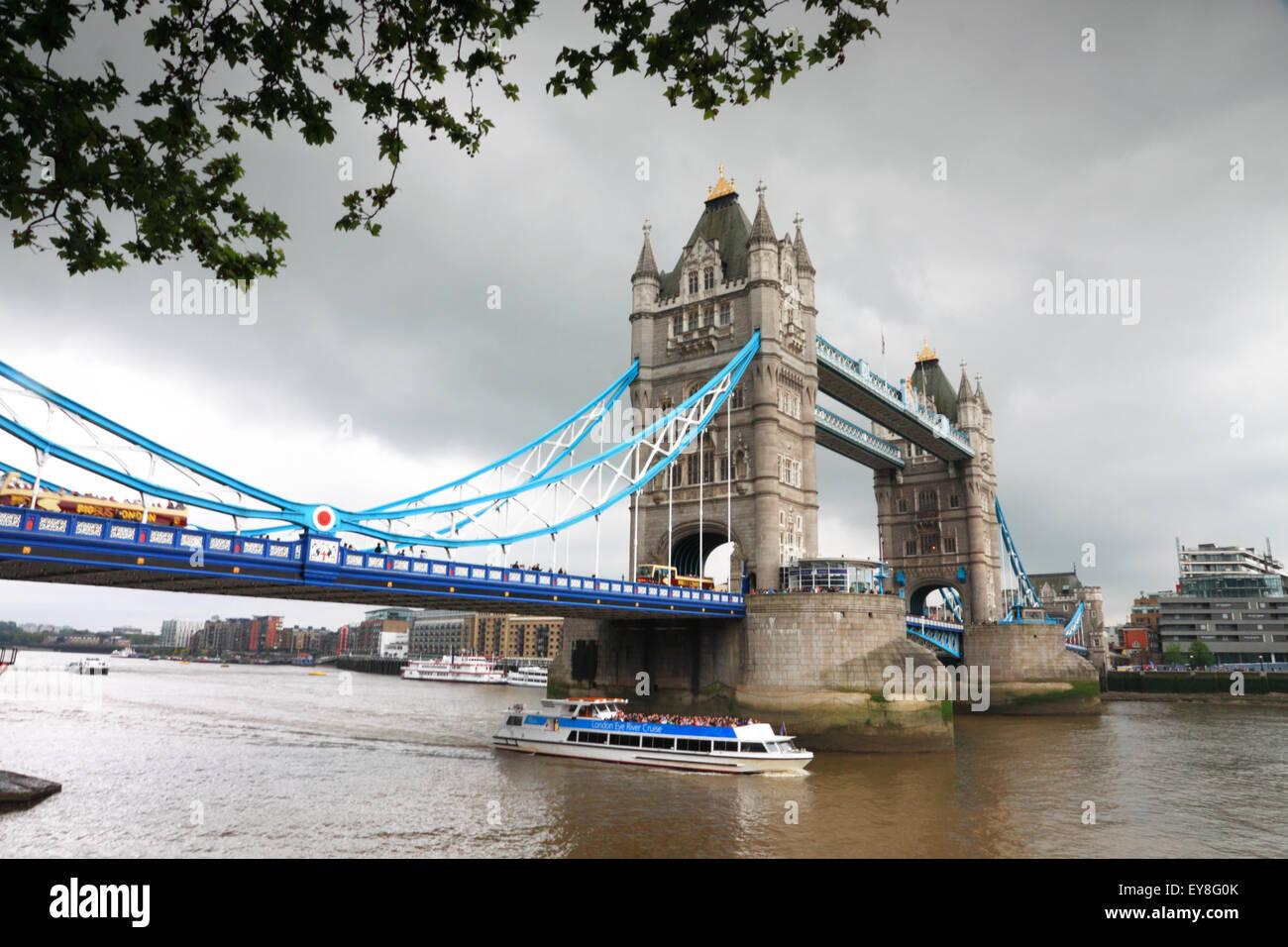 Tower Bridge, London, umrahmt von Bäumen an einem grauen Tag und ein Touristenboot auf dem Fluss. Stockbild