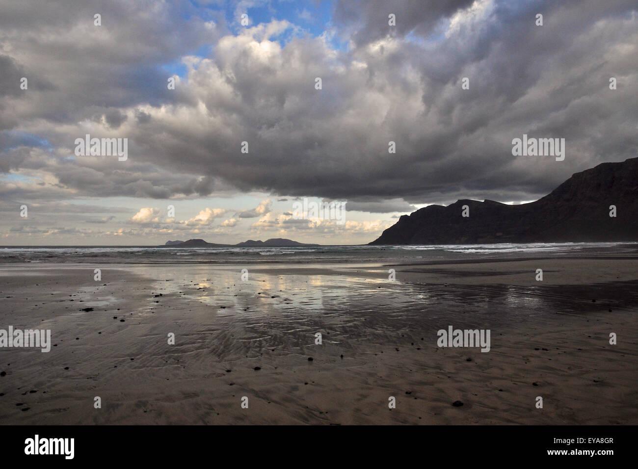 Der Strand von Famara Strand bei Ebbe mit reflektierte Wolken und Chinijo Archipel im fernen Ende (Lanzarote, Kanarische Stockbild