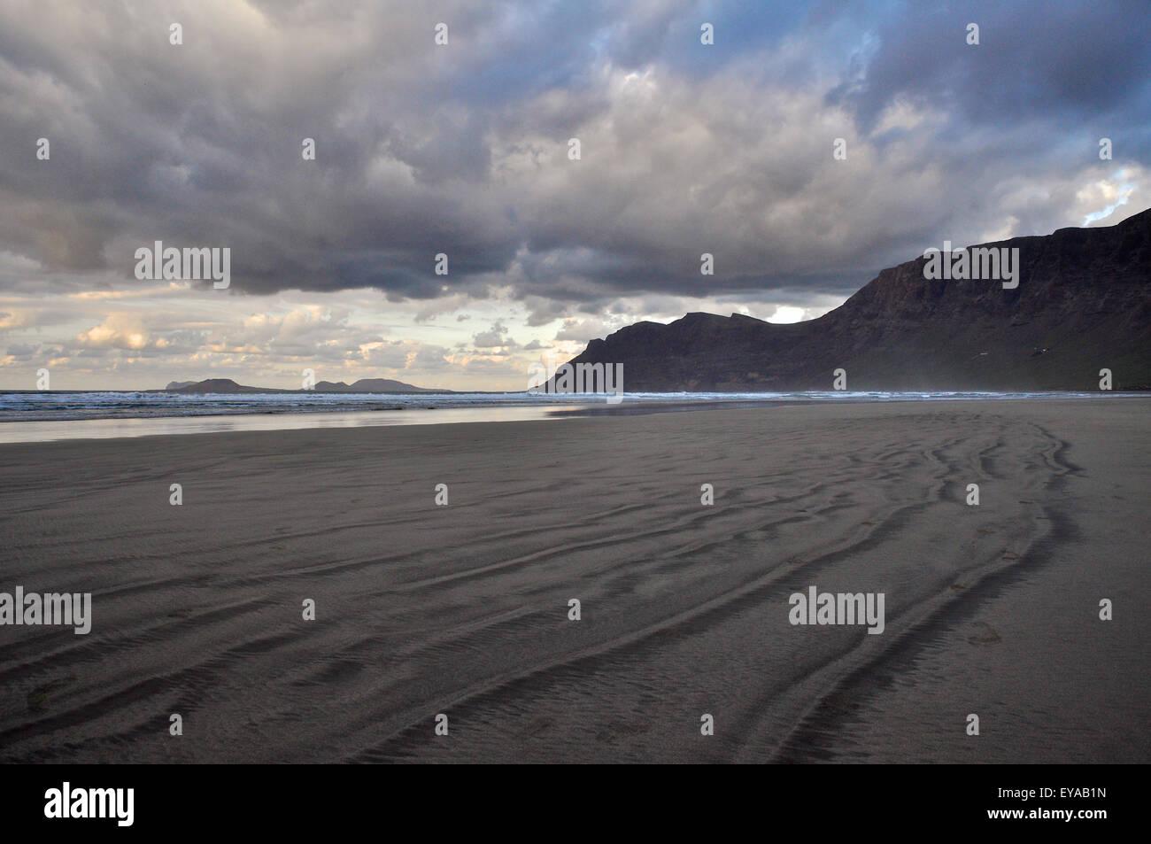 Der Strand von Famara Strand bei Ebbe mit Sand Linien, große Wolken und Chinijo Archipel im fernen Ende (Lanzarote, Stockbild