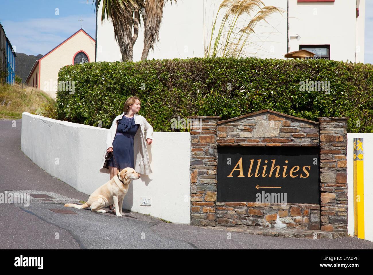 Eine Frau, die durch ein Schild für ihr Dorf mit ihrem Golden Retriever; Allihies, County Cork, Irland Stockfoto