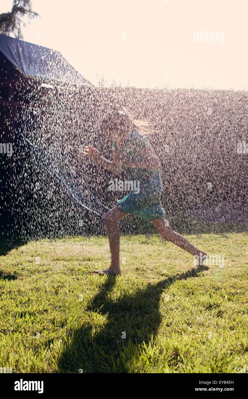Mädchen aus einem Garten Sprinkler durch Spritzwasser läuft. Stockbild