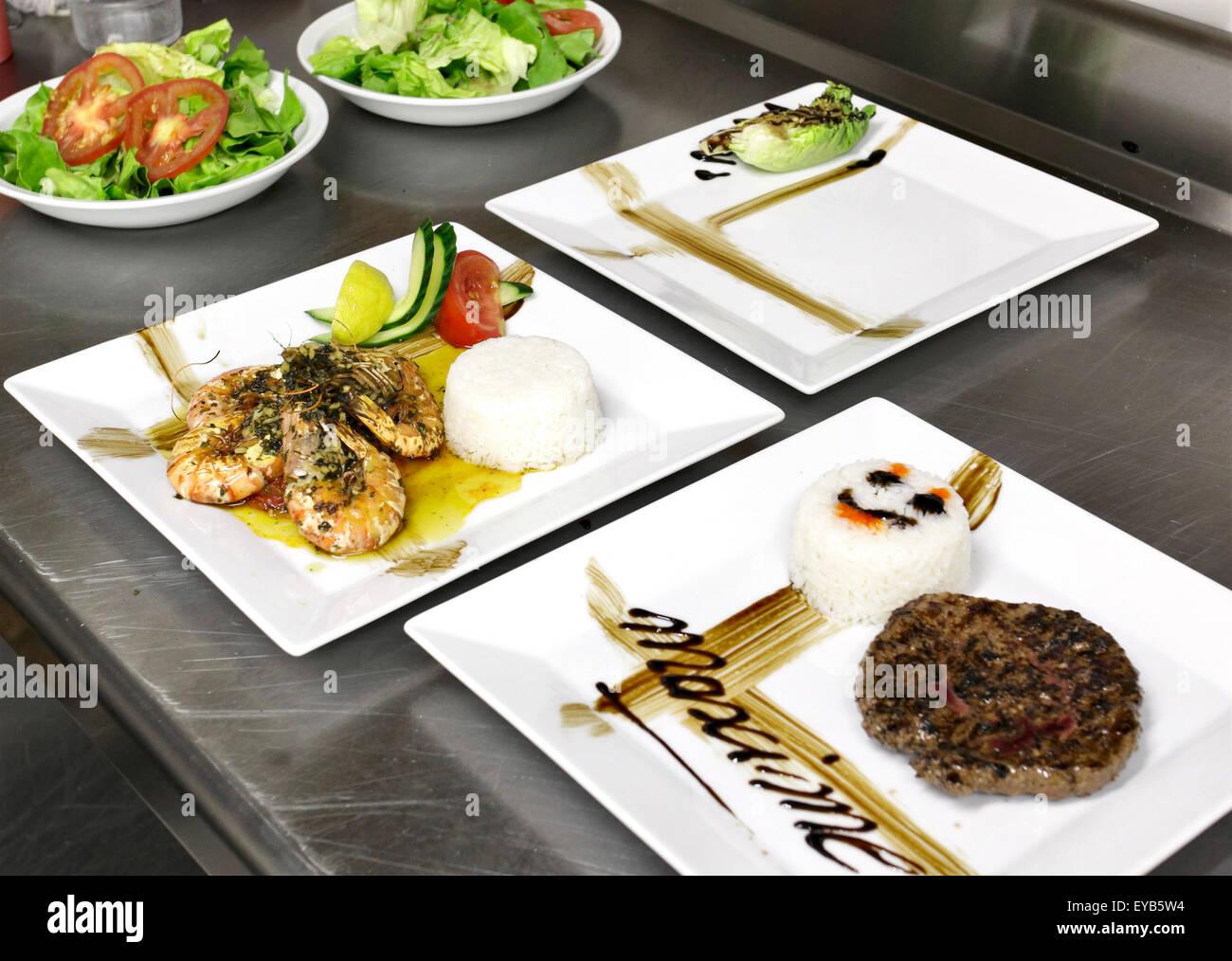 italienische Küche: Burger in quadratische Schale, Garnelen und Gemüse Stockbild