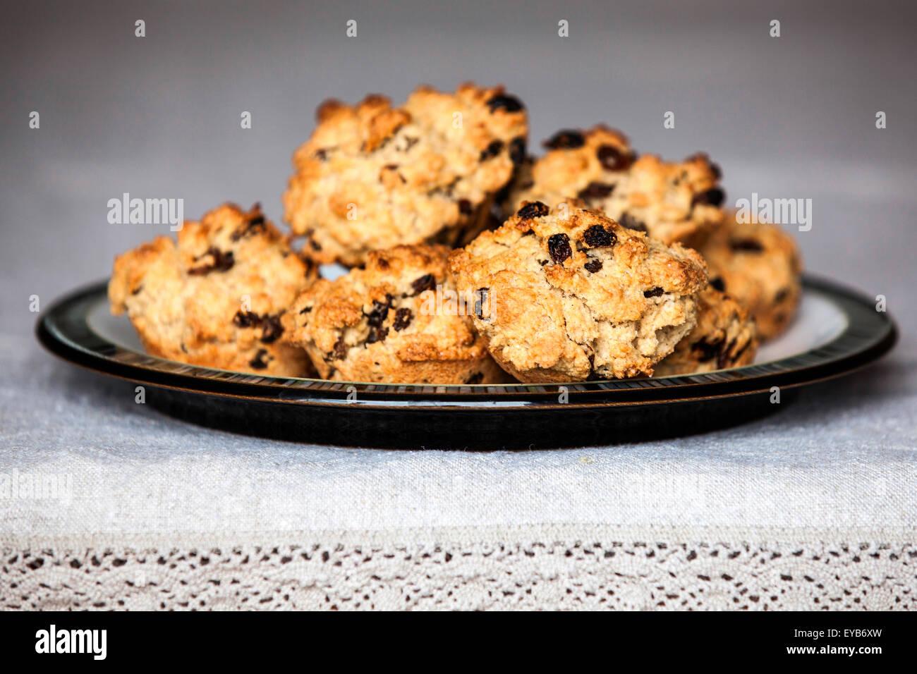 Eine Platte der frisch gebackene rock Kuchen auf eine Platte auf einem Tisch mit einem leinen Tischdecke platziert Stockbild