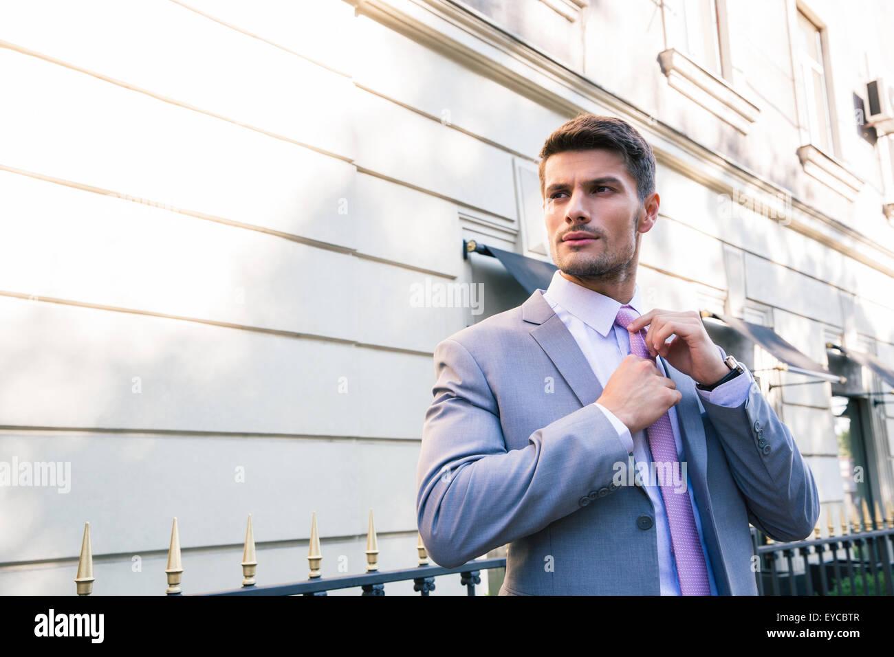 Gut aussehend Geschäftsmann richtet seine Krawatte im freien Stockbild