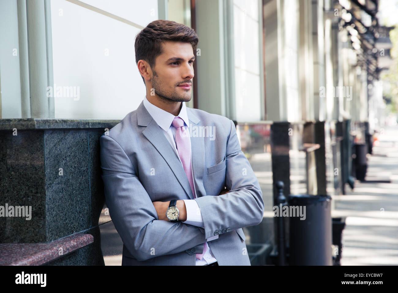 Porträt eines nachdenklich Geschäftsmann mit Arme gefaltetes stehen draußen in der Stadt Stockbild