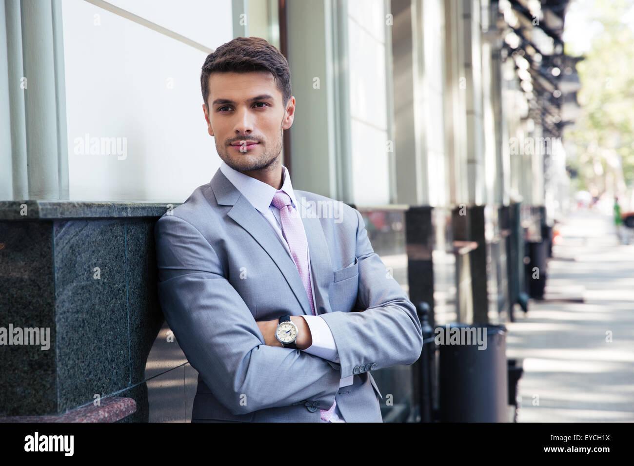 Porträt eines schönen Geschäftsmann mit Arme gefaltetes stehen draußen in der Stadt Stockbild