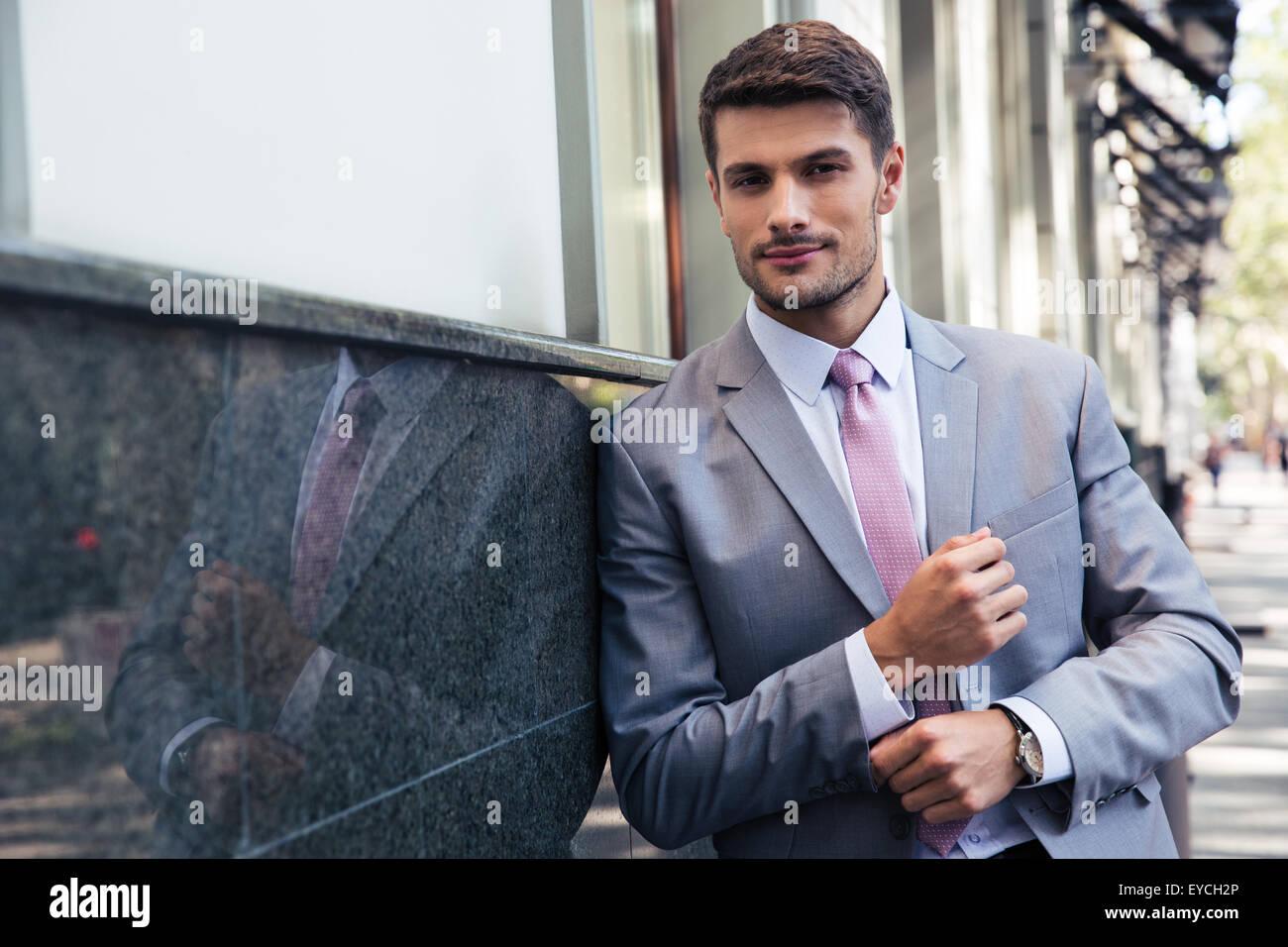 Zuversichtlich Geschäftsmann stehen im Freien und Blick in die Kamera Stockbild