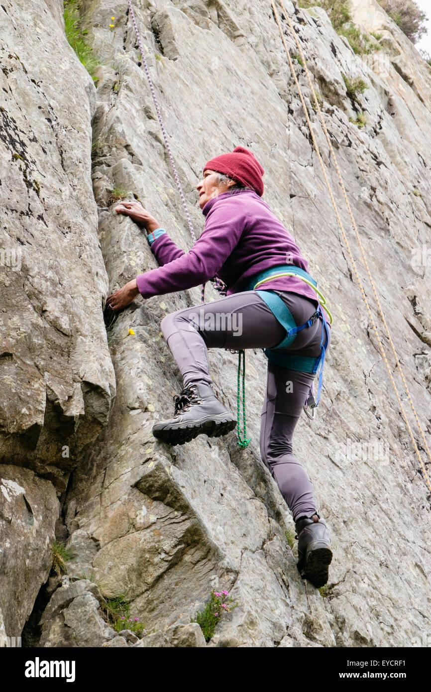 Ältere Frau weibliche Bergsteiger mit Sicherheit Toprope Klettern auf Felsen Riss in eine steile Felswand. Stockbild