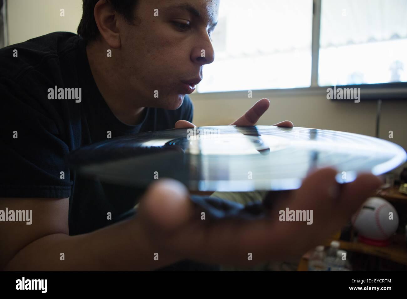 Nahaufnahme von junger Mann bläst Oberfläche Vinyl-Schallplatte Stockbild