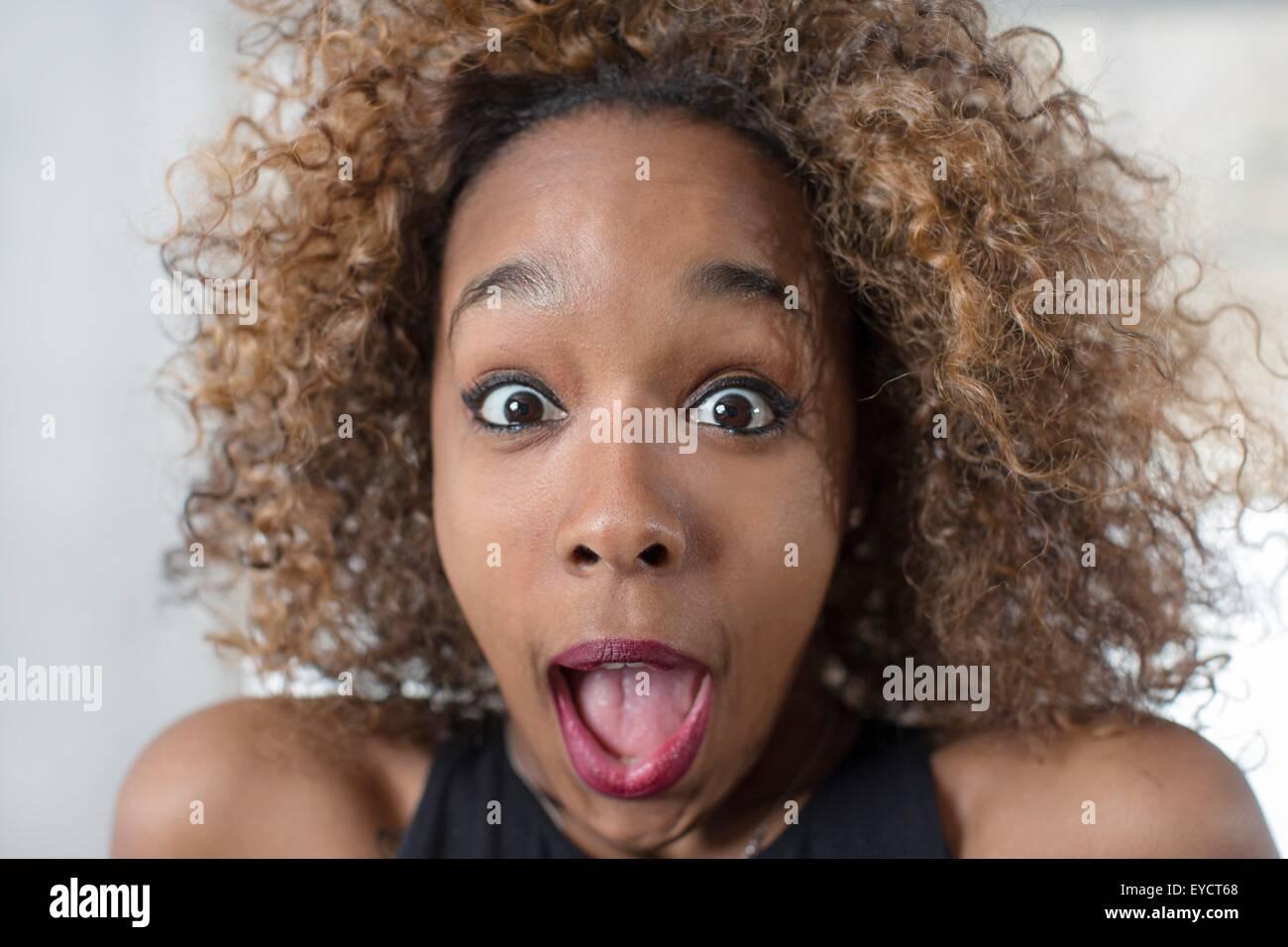 Porträt der jungen Frau zieht ein Gesicht und Mund öffnen Stockfoto