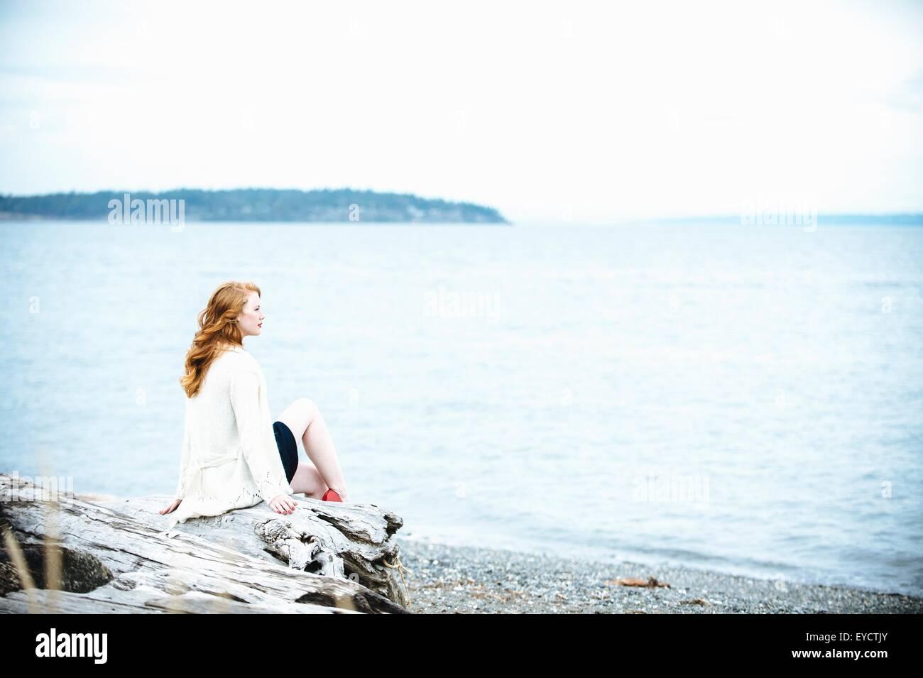 Junge Frau sitzt am Strand mit Blick auf Meer, Bainbridge Island, Washington State, USA Stockbild