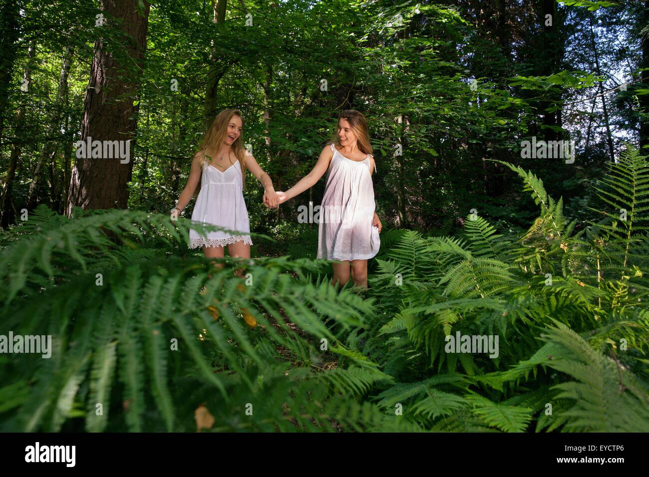 Zwei Mädchen im Teenageralter durch Wald, hand in hand gehen Stockbild