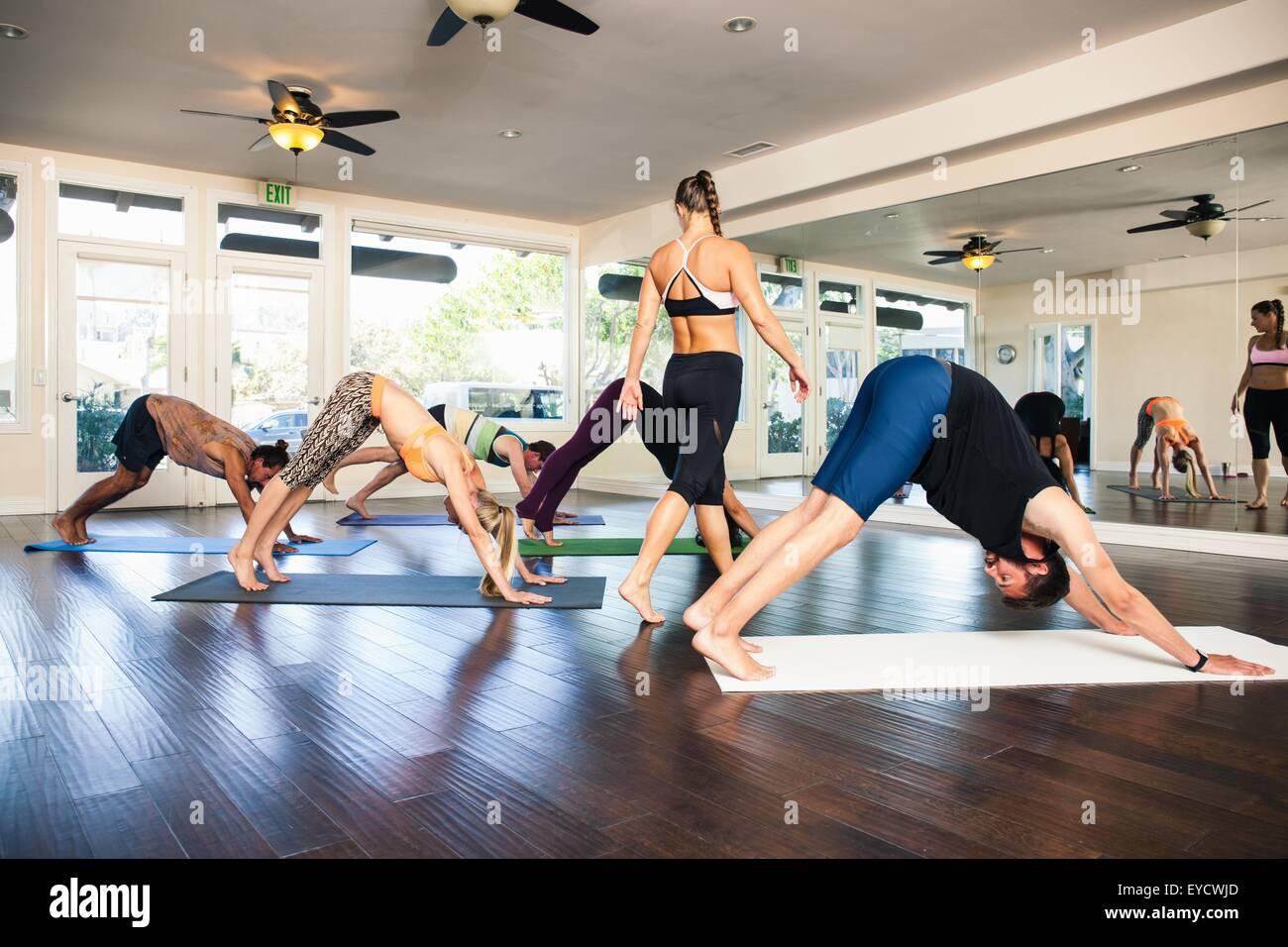 Yoga-Lehrer in der Klasse mit Menschen unten Hund Position Stockbild
