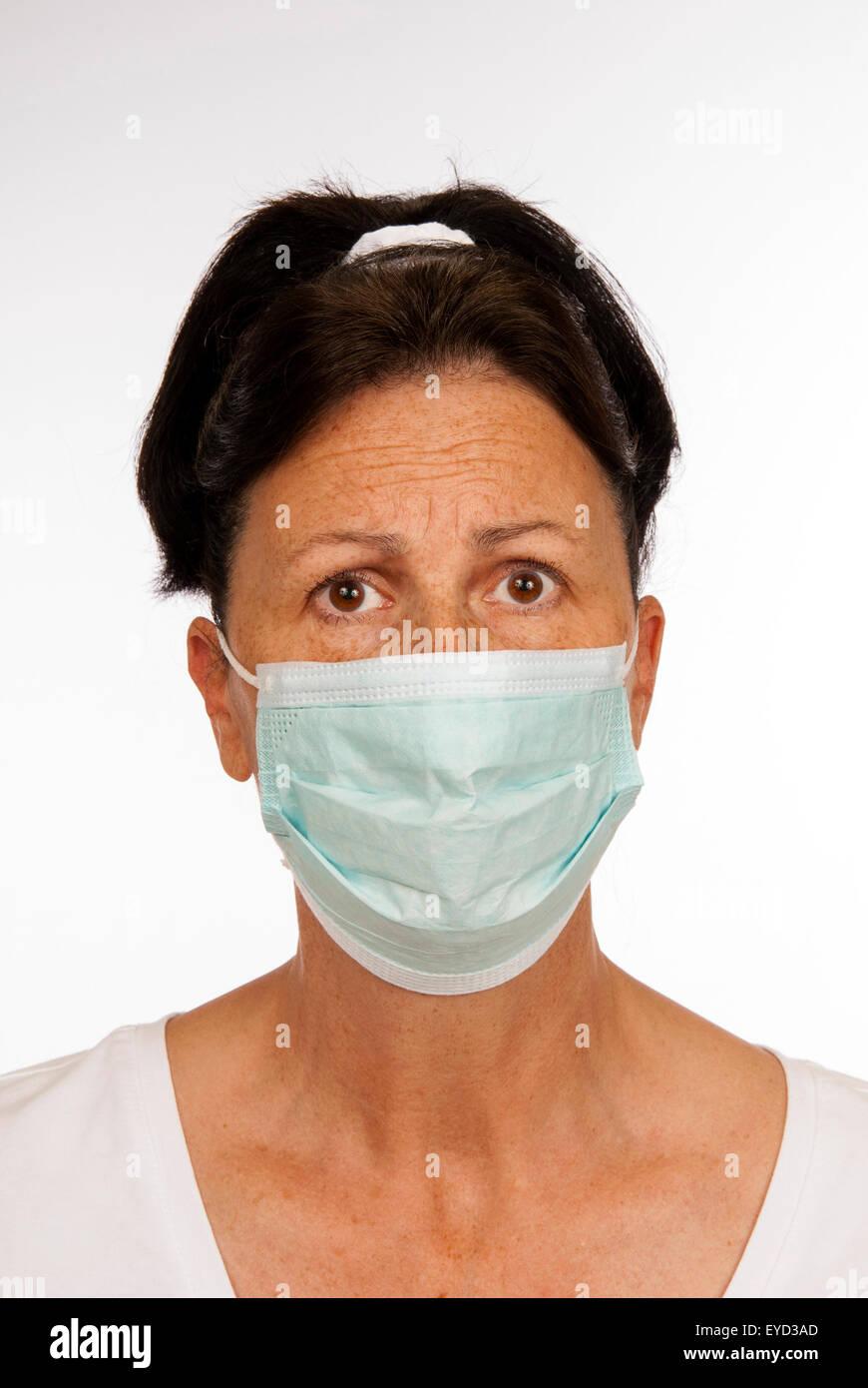 Frau auf der Suche besorgt über den Fang einer ansteckenden Krankheit und eine medizinische Maske trägt. Stockbild